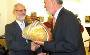 Páva Zsolt pécsi polgármester (jobbról) átnyújtja Bognár Levente aradi alpolgármesternek a reggel Pécsett sütött Magyarok kenyerét